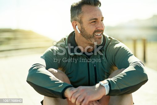 Shot of a mature man using wireless earphones while out for his workout