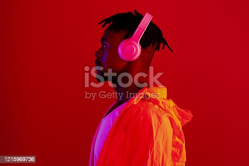 Red filtered shot of a young sportsman wearing headphones while posing in the studio