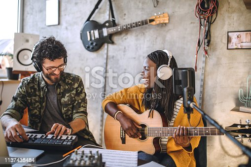 Happy, young couple smiling lively while recording music at home