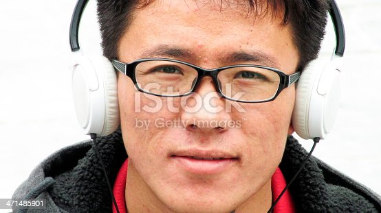 Close up portrait of a young adult male listening to music with headphone on