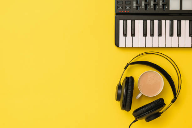 Music mixer and black headphones and coffee on yellow background. The view from the top. stock photo
