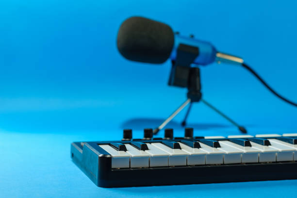 Music mixer and blue microphone with wires on blue background. stock photo