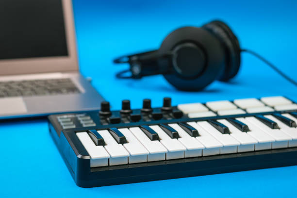 Music mixer and headphones and laptop on blue background. stock photo