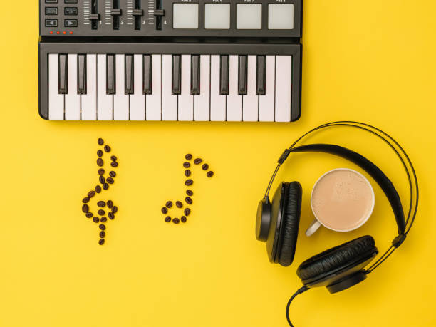 Music mixer, coffee bean notes and headphones on yellow background. The concept of writing music. The view from the top. stock photo