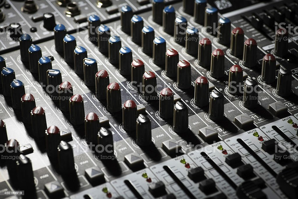 Detail of a music mixer desk with various knobs