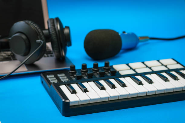 Music mixer, laptop and blue microphone with wires on blue background. stock photo