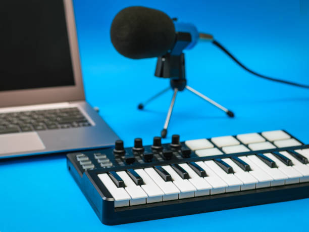 Music mixer, laptop and microphone with wires on blue background. stock photo