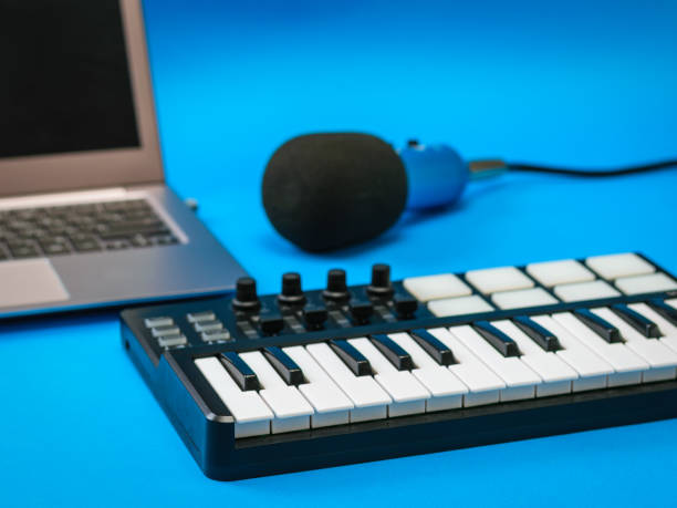 Music mixer, open laptop and microphone with wires on blue background. stock photo