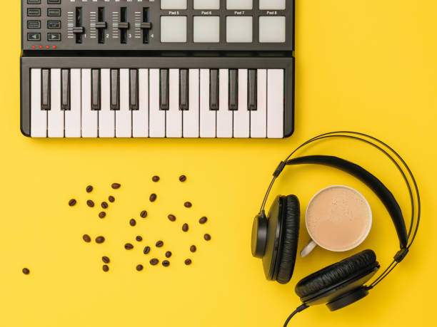 Music mixer, scattered coffee beans, headphones and a Cup of coffee on a yellow background. The view from the top. stock photo