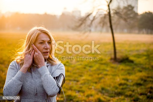 851958232istockphoto Music motivation for runnng, mature woman walking 629254220