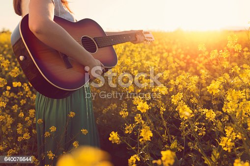 Close-up of an unrecognizable female playing acoustic guitar in the nature.