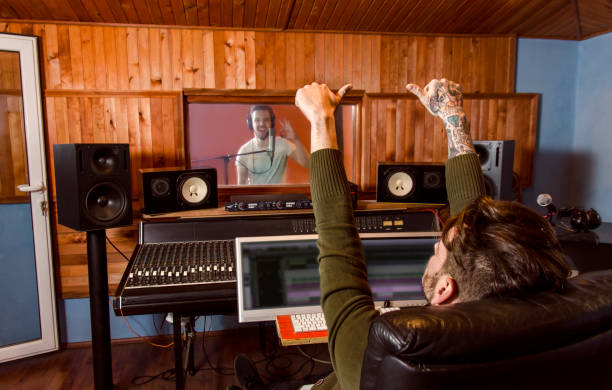 Music producer and singer/artist in other room thumbs up stock photo
