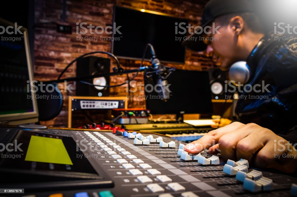 music producer working on sound mixer in recording studio or DJ working in broadcasting studio stock photo
