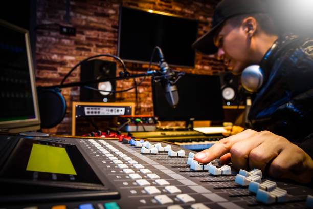 music producer working on sound mixer in recording studio or dj working in broadcasting studio - radio station stock photos and pictures