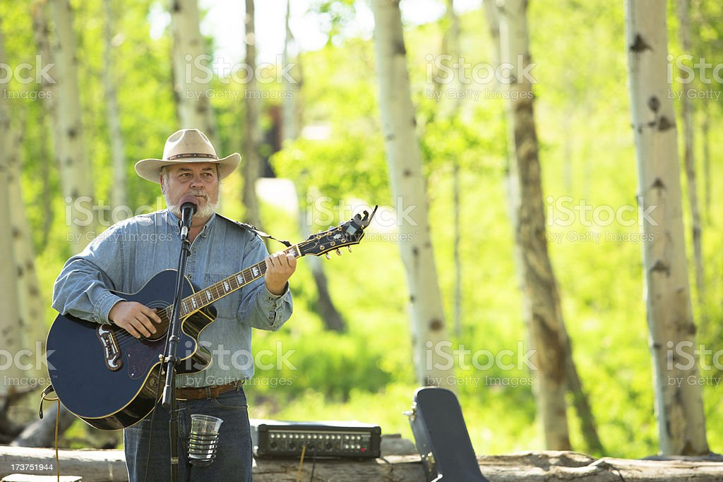 Music: Senior Cowboy sings, plays guitar at outdoor BBQ. royalty-free stock photo