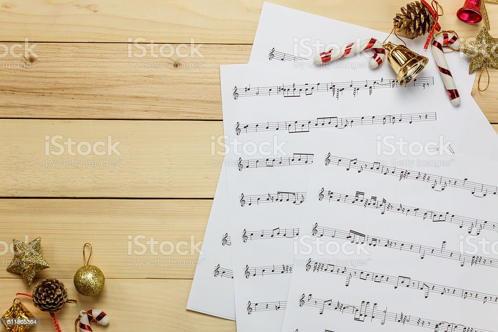 music sheet note paper and christmas decoration on wood background. stock photo