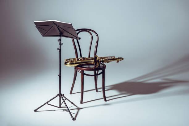 notenständer für notizen und saxophon auf stuhl im studio - notenständer stock-fotos und bilder