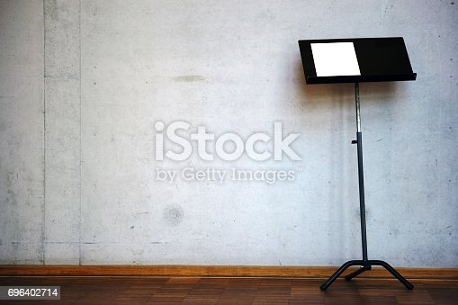 The close up of a music stand against a striking concrete wall.