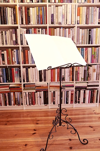 Music stand with open white sheets in front of book shelves