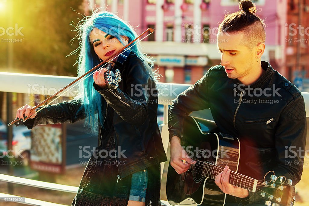 Music street performers with girl violinist sunset cityscape. stock photo