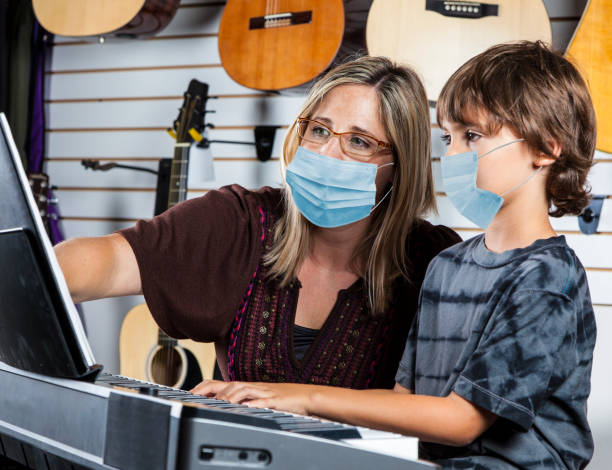Music teacher and student at piano playing wearing protective face masks. stock photo