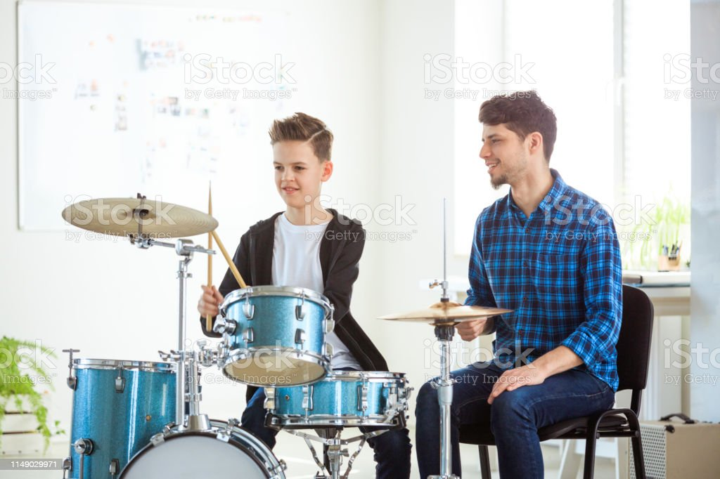 Music teacher explaining boy to play drums Male music teacher explaining little drummer. Pre-adolescent boy is listening to mid adult instructor. They are practicing in conservatory. 12-13 Years Stock Photo