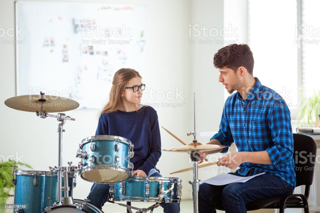 Music teacher explaining girl to play drums Male music teacher explaining female drummer. Pre-adolescent girl is listening to mid adult instructor. They are practicing in conservatory. 10-11 Years Stock Photo