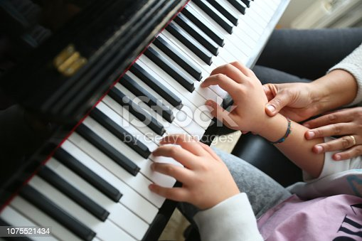 A music teacher is teaching her student how to play the piano.