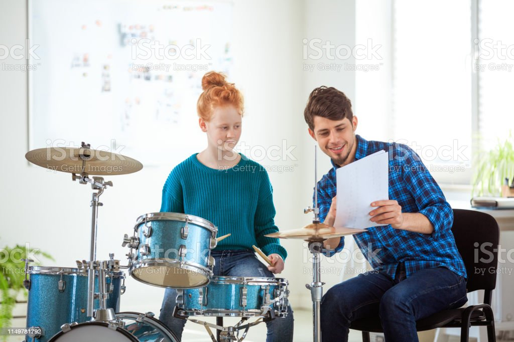 Music teacher showing sheet to female student Smiling music teacher showing sheet to pre-adolescent student. Female drummer is practicing by instructor. They are in conservatory. 12-13 Years Stock Photo