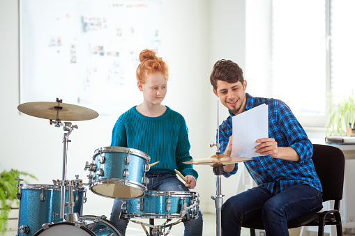 Music Teacher Showing Sheet To Female Student Stock Photo - Download Image Now