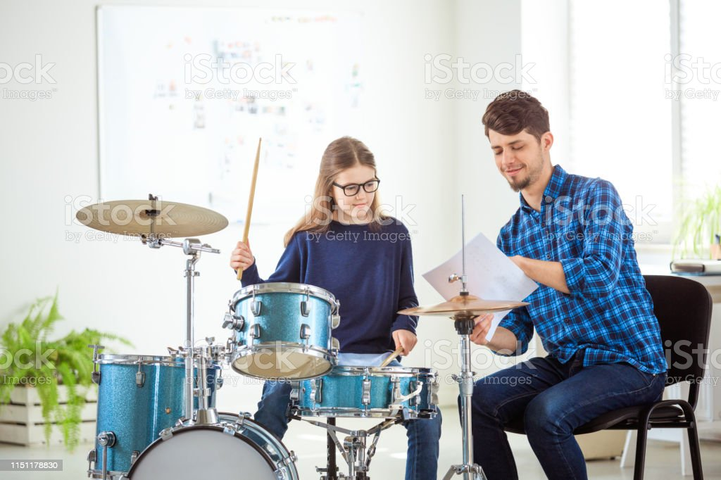 Music teacher teaching drummer in conservatory Male music teacher showing sheet to pre-adolescent student. Female drummer is practicing with instructor. They are sitting in conservatory. 10-11 Years Stock Photo