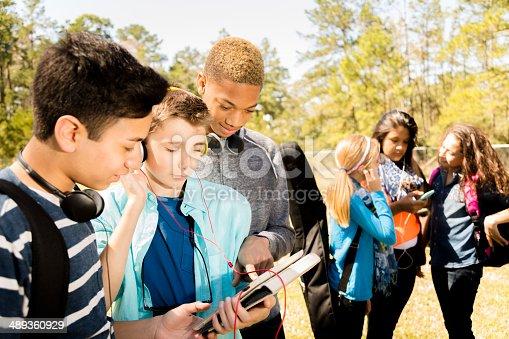 istock Music: Teenage friends listen to music on digital tablet.  Park. 489360929