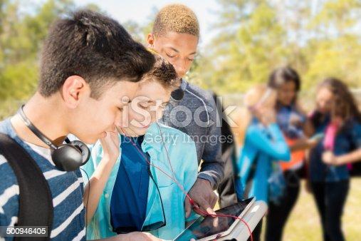 istock Music: Teenage friends listen to music on digital tablet.  Park. 500946405
