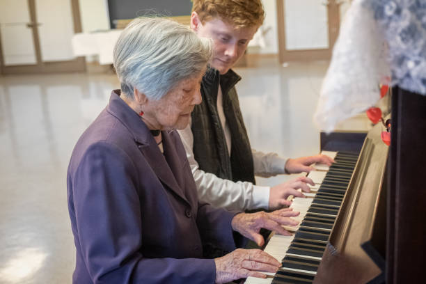 Music Therapy, Senior Asian Woman Playing Piano with Young Man stock photo