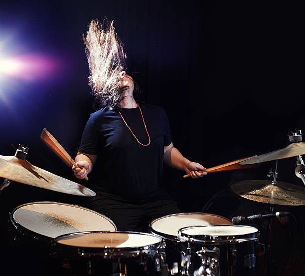 Music to bang her head to! Shot of a young woman rocking out on drumshttp://195.154.178.81/DATA/i_collage/pu/shoots/806435.jpg drummer stock pictures, royalty-free photos & images