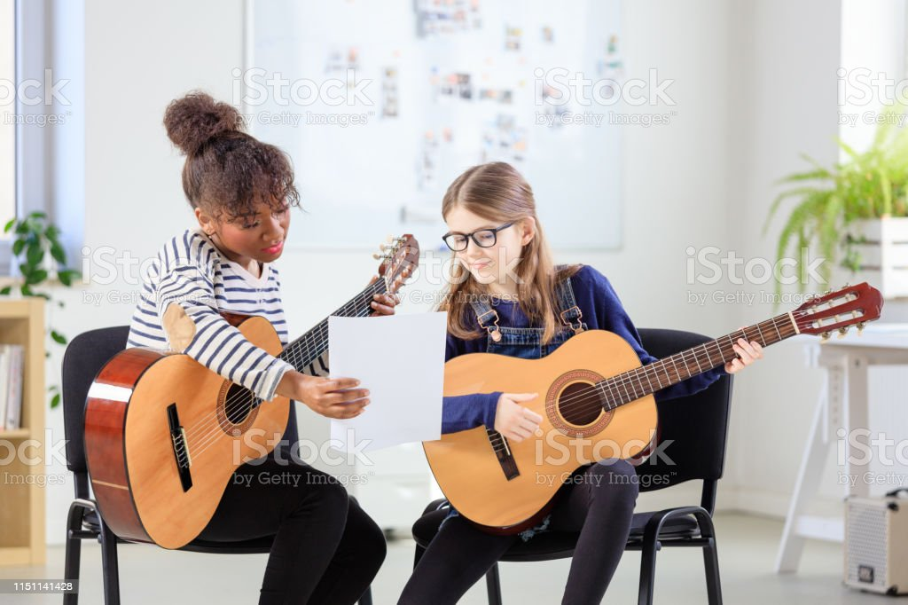 Music trainer showing sheet to female student Trainer showing sheet to student while practicing guitar. Pre-adolescent guitarist is learning with teacher in in training class. They are at education building. 10-11 Years Stock Photo
