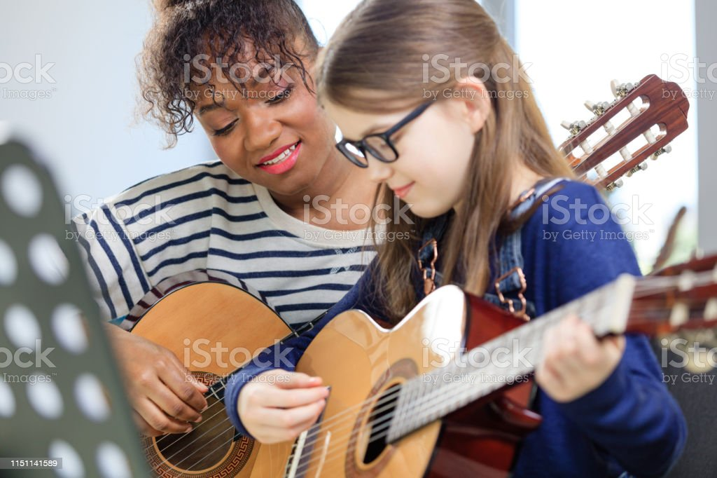 Music trainer teaching student plucking guitar Smiling guitarist teaching student plucking guitar in classroom. Pre-adolescent girl is learning string instrument from female teacher. They are in training class at conservatory. 10-11 Years Stock Photo