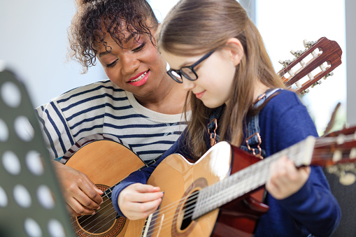 Music Trainer Teaching Student Plucking Guitar Stock Photo - Download Image Now
