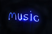 Music written with blue lights with a black background. Studio shot