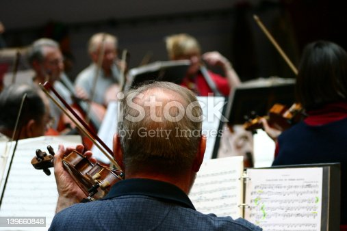 close up picture of musical instruments during a classical concert music: older violin player pictured from back