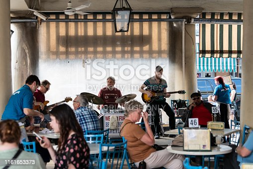 New Orleans, USA - April 23, 2018: Musical band playing guitar and drums instruments live concert performance at Cafe Du Monde famous beignet and chicory coffee restaurant with people