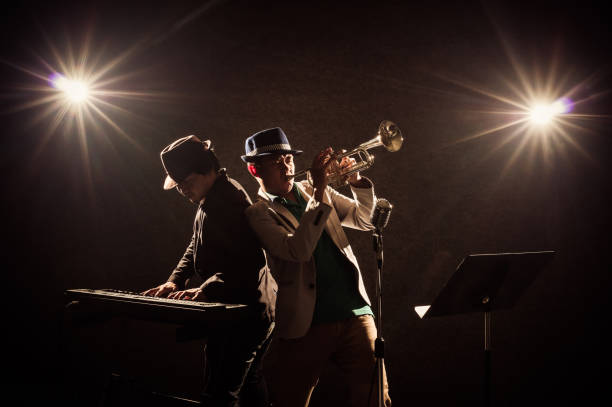 musical concept, musicians playing a trumpet and keyboard - performance group stock photos and pictures