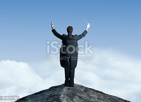 A rear view of a musical conductor standing on top of a mountain top.  He has his arms raised with a baton in one hand as he is preparing to lead the orchestra.  Before him, and in the distance, white puffy clouds sit below a clear blue sky.