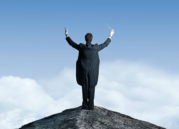 Musical Conductor On Top Of Mountain Top With Arms Raised - foto de stock