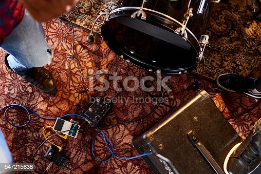 Musical instruments plugged into amplifier on carpet