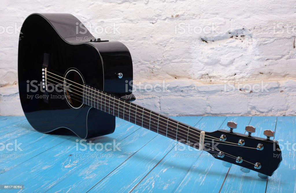 Musical instrument - Black cutaway acoustic guitar brick background stock photo