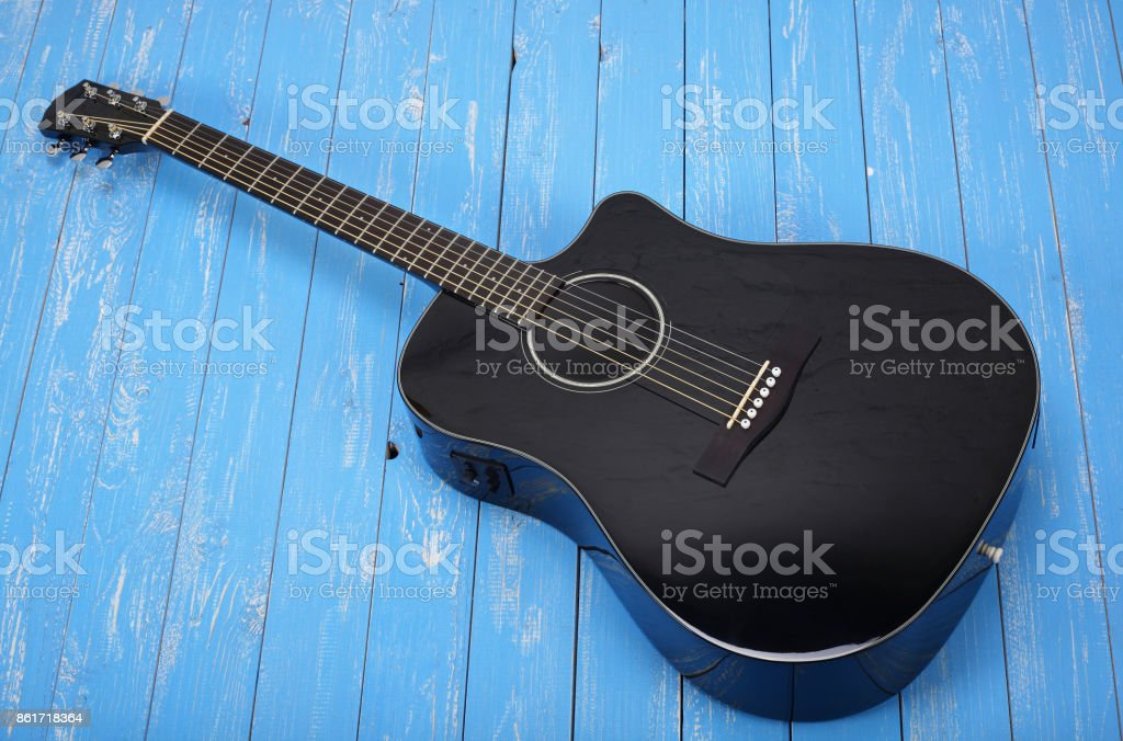 Musical instrument - Black cutaway electric acoustic guitar wood background stock photo