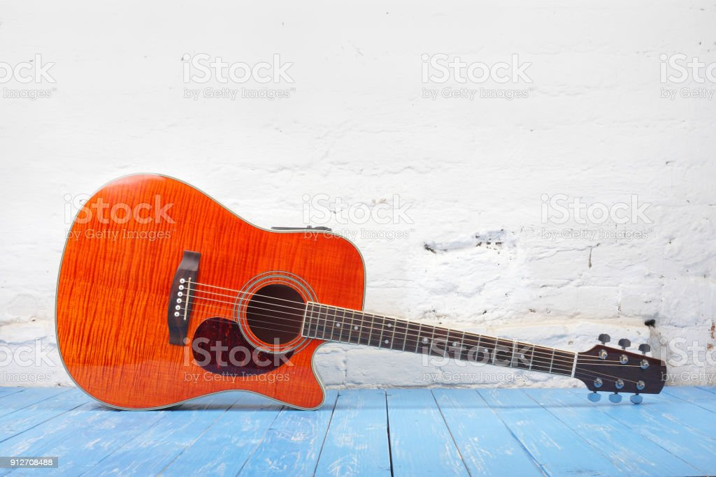 Musical instrument - Orange flame maple acoustic guitar brick background stock photo