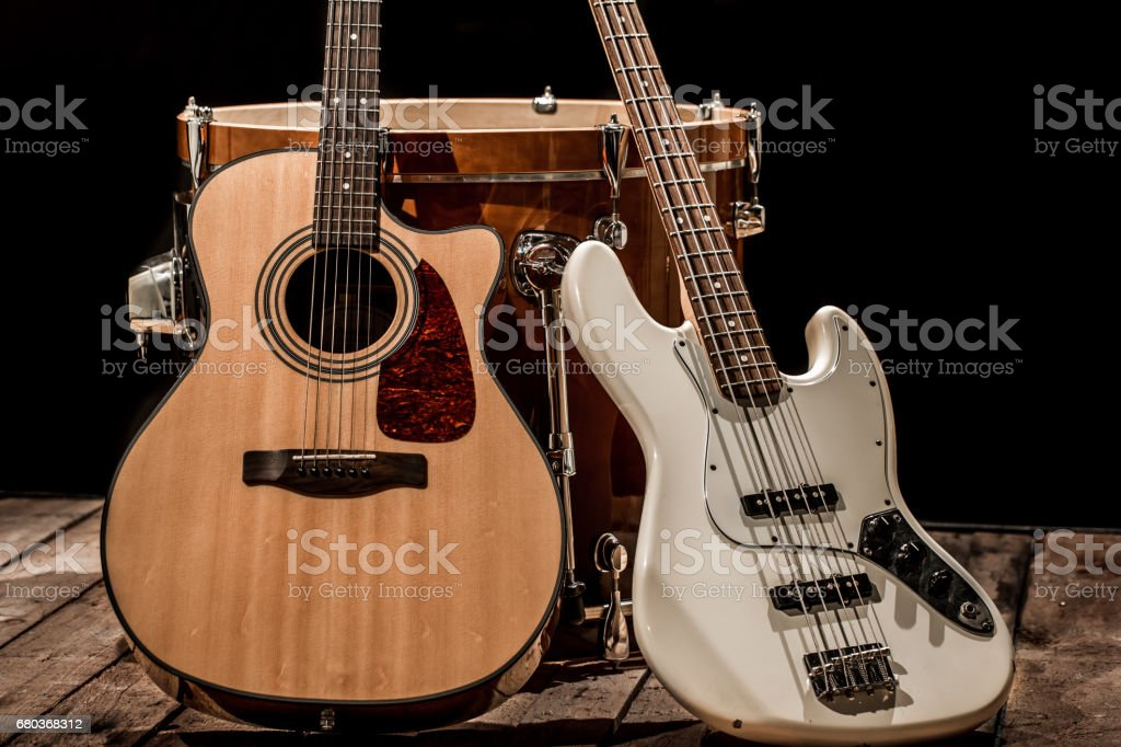 musical instruments, bass drum barrel acoustic guitar and bass guitar on a black background stock photo
