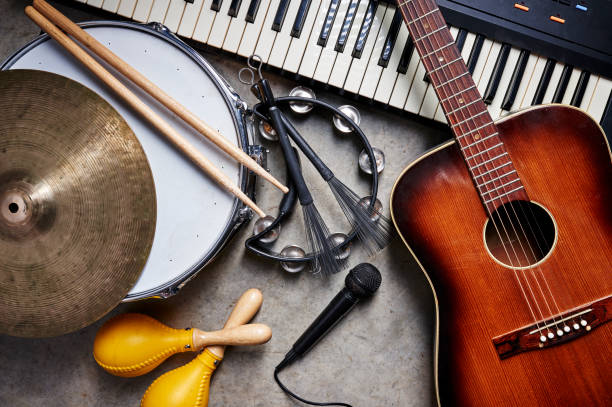 musical instruments a group of musical instruments including a guitar, drum, keyboard, tambourine. synthesizer stock pictures, royalty-free photos & images